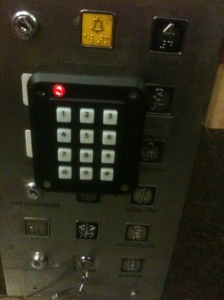 A picture of a control panel in an elevator showing the numbers used to control the lift. On top of those numbers is an extra panel bolted on with another set of buttons - confusing!